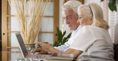 anciano y anciana consultando en el ordenador