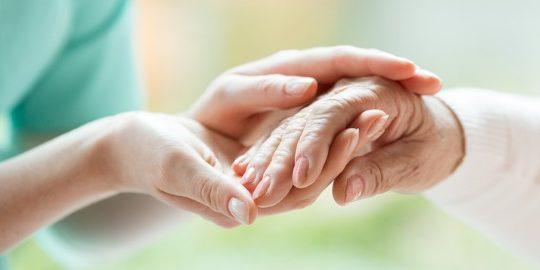 enfermera coge mano de anciano