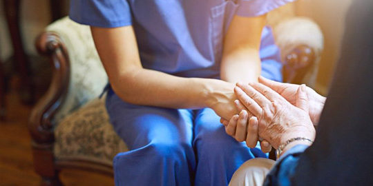 enfermera y anciana se dan la mano