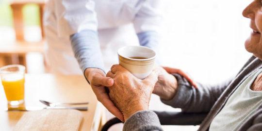 enfermera lleva una bebida a un anciano