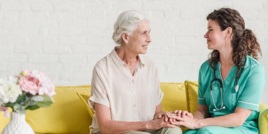 Enfermera habla con paciente mayor